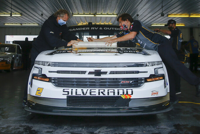Crew members for Sheldon Creed wrap up the truck after the NASCAR Truck Series auto race scheduled for Saturday afternoon, June 27, 2020, was postponed to the next morning due to weather at Pocono Raceway, in Long Pond, Pa. (AP Photo/Matt Slocum)