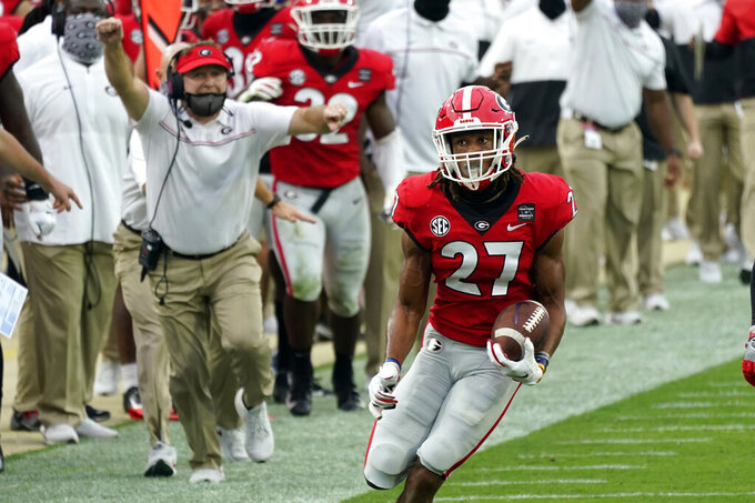Georgia head coach Kirby Smart, left, cheers on defensive back Eric Stokes (27) as he returns a Florida interception for a 37-yard touchdown during the first half of an NCAA college football game, Saturday, Nov. 7, 2020, in Jacksonville, Fla. (AP Photo/John Raoux)