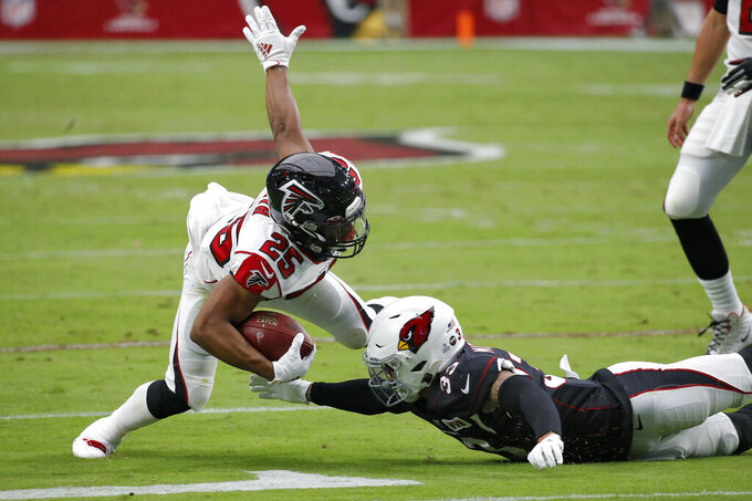 Atlanta Falcons running back Ito Smith (25) is hit by Arizona Cardinals cornerback Byron Murphy (33) during the first half of an NFL football game, Sunday, Oct. 13, 2019, in Glendale, Ariz. (AP Photo/Ross D. Franklin)