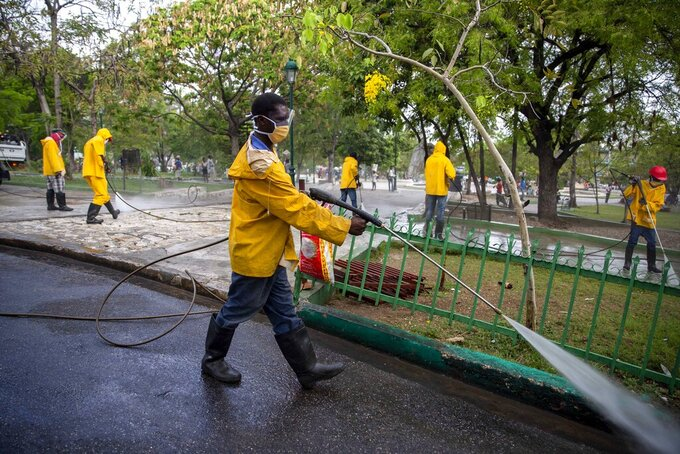 FILE - In this April 7, 2020 file photo, City Hall workers spray disinfectant in the street and a park in Petion-Ville, Haiti. To help contain the spread of the new coronavirus, the mayor of Petion-Ville announced public markets would reduce their operation to three days a week, public transportation would limit passengers to eight per muni-bus and Tap-tap buses, and passengers would be required to wear face masks. (AP Photo/Dieu Nalio Chery, File)
