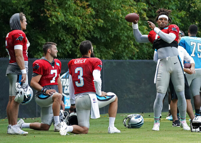 Carolina Panthers' Cam Newton (1) warms up as fellow quarterbacks, from left to right, Taylor Heinicke, Kyle Allen and Will Grier watch during practice at the NFL football team's training camp in Spartanburg, S.C., Sunday, July 28, 2019. (AP Photo/Chuck Burton)