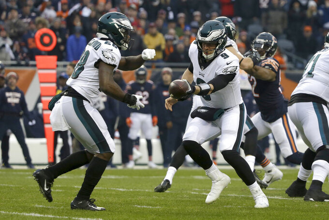 Philadelphia Eagles quarterback Nick Foles (9) hands off the ball to running back Wendell Smallwood (28) during the first half of an NFL wild-card playoff football game against the Chicago Bears Sunday, Jan. 6, 2019, in Chicago. (AP Photo/David Banks)