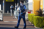 """FILE - In this Saturday, Sept. 4, 2021, file photo, armed police patrol outside a supermarket in Auckland, New Zealand. Ahamed Aathil Samsudeen grabbed a kitchen knife from store shelf and begins stabbing shoppers while chanting """"Allahu akbar"""" — meaning """"God is great"""" at the supermarket on Sept. 3, 2021. (AP Photo/Brett Phibbs, File)"""