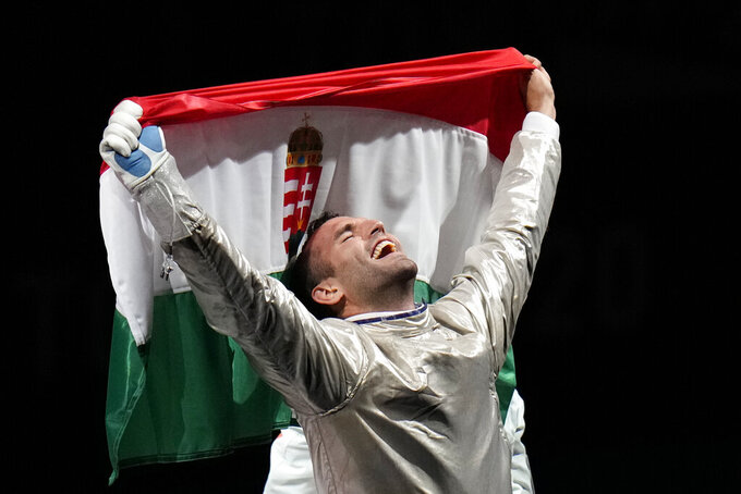 Aron Szilagyi of Hungary celebrates winning the gold medal after defeating Luigi Samele of Italy compete in the men's individual final Sabre competition at the 2020 Summer Olympics, Saturday, July 24, 2021, in Chiba, Japan. (AP Photo/Hassan Ammar)