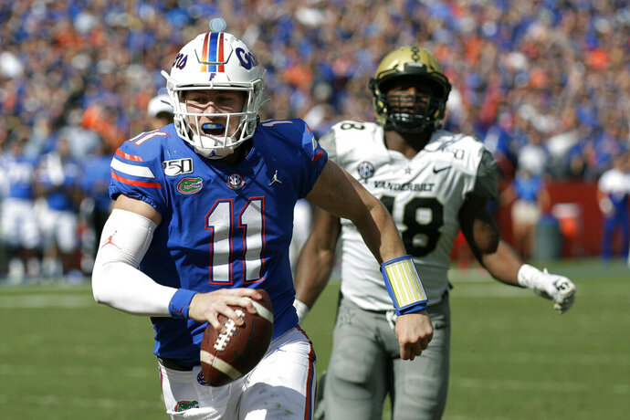 Florida quarterback Kyle Trask (11) runs past Vanderbilt linebacker Andre Mintze for a 9-yard touchdown during the first half of an NCAA college football game, Saturday, Nov. 9, 2019, in Gainesville, Fla. (AP Photo/John Raoux)