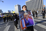 A mourner with a portrait of the deceased Kim Bok-dong, a former South Korean sex slave, marches towards the Japanese Embassy during her funeral ceremony in Seoul, South Korea, Friday, Feb. 1, 2019. Hundreds of mourners gathered Friday near the embassy for the funeral of Kim forced as a girl into a brothel and sexually enslaved by the Japanese military in WWII. (AP Photo/Ahn Young-joon)