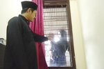 Dr. Irman Pahlepi talks with his family from inside house during a self-isolation in Jakarta, Indonesia, on July 29, 2021. Pahlepi is back at work in Jakarta's Dr. Suyoto public hospital, immediately resuming his duties treating COVID-19 patients after recovering from an infection himself, for the second time. With numbers of infections in Indonesia skyrocketing and deaths steadily climbing, health care workers are being depleted as the virus spares nobody, Pahlepi felt he had no option but to jump right back in. (AP Photo/Irman Pahlepi)