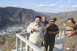 In this undated photo provided on Wednesday, Oct. 14, 2020, by the North Korean government, North Korean leader Kim Jong Un, left, visits the typhoon-ravaged rural town of Komdok, North Korea, to inspect recovery works. Kim's inspection was his first public activity after weekend celebrations marking his ruling party's founding anniversary. Independent journalists were not given access to cover the event depicted in this image distributed by the North Korean government. The content of this image is as provided and cannot be independently verified. Korean language watermark on image as provided by source reads: