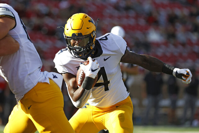 West Virginia's Leddie Brown (4) runs the ball to score a touchdown during the first half of an NCAA college football game against Texas Tech, Saturday, Oct. 24, 2020, in Lubbock, Texas. (AP Photo/Brad Tollefson)