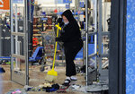 A woman cleans up debris at a Walmart, Wednesday, Oct. 28, 2020, that was damaged in protests in Philadelphia. Demonstrators protested the death of Walter Wallace Jr., who was fatally shot by police Monday after authorities say he ignored orders to drop a knife. Some businesses were cleaning up damage after video showed people streaming into stores and stealing goods on the opposite side of the city from where Wallace was shot. (AP Photo/Michael Perez)