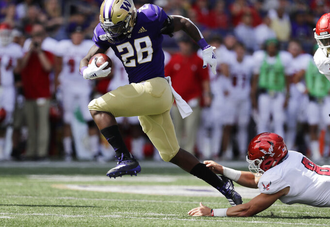 Washington's Richard Newton (28) escapes a tackle-attempt by Eastern Washington's Jack Sendelbach to score a touchdown in the first half of an NCAA college football game Saturday, Aug. 31, 2019, in Seattle. (AP Photo/Elaine Thompson)