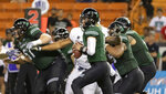 Hawaii quarterback Cole McDonald, center, looks for an open receive to pass to in the first half of an NCAA college football game against Utah State, Saturday, Nov. 3, 2018, in Honolulu. (AP Photo/Eugene Tanner)