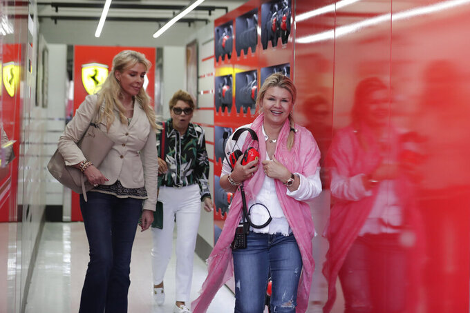 Mick Schumacher's mother Corinna, right, leaves Ferrari garage during her son first F1 test for Ferrari at the Bahrain International Circuit in Sakhir, Bahrain, Tuesday, April 2, 2019. Mick Schumacher has moved closer to emulating his father Michael by driving a Ferrari Formula One car in an official test. Schumacher's father won seven F1 titles, five of those with Ferrari and holds the record for race wins with 91. (AP Photo/Hassan Ammar)