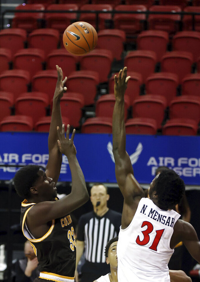 Wyoming forward Graham Ike (33) shoots as San Diego State forward Nathan Mensah (31) defends during the second half of an NCAA college basketball game in the quarterfinal round of the Mountain West Conference men's tournament Thursday, March 11, 2021, in Las Vegas. (AP Photo/Isaac Brekken)
