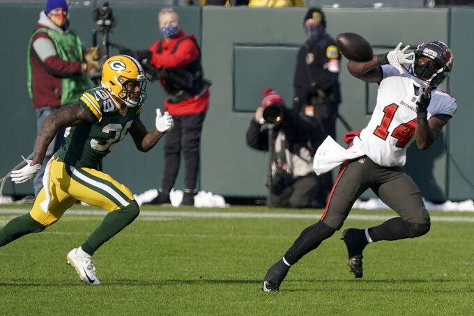 Tampa Bay Buccaneers' Chris Godwin grabs a pass while being chased by Green Bay Packers' Chandon Sullivan during the first half of the NFC championship NFL football game in Green Bay, Wis., Sunday, Jan. 24, 2021. (AP Photo/Morry Gash)