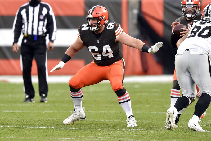 FILE - In this Sunday, Nov. 1, 2020, file photo, Cleveland Browns center JC Tretter (64) blocks during an NFL football game against the Las Vegas Raiders in Cleveland. Browns center JC Tretter, president of the players' union, has called for all NFL stadiums to put in natural grass fields; this season, 17 stadiums have it, while 13 have synthetic surfaces.  (AP Photo/David Richard, File)