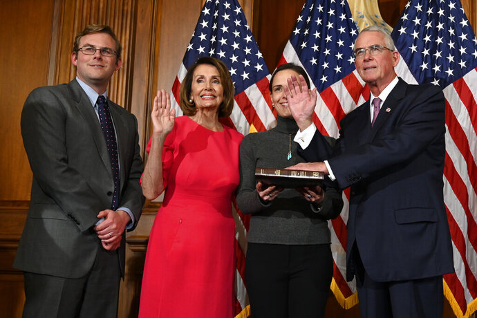 "FILE - In this Jan. 3, 2019, file photo, House Speaker Nancy Pelosi of Calif., second from left, poses during a ceremonial swearing-in with Rep. Francis Rooney, R-Fla., right, on Capitol Hill in Washington. said out loud Friday, Oct. 19, what others in his party are not, namely that White House Chief of Staff Mick Mulvaney acknowledged a ""quid pro quo"" was at work when Trump held up U.S. aid to Ukraine in exchange for Kyiv's investigation of Democrats and the 2016 elections. Mulvaney later claimed his comments had been misconstrued, but Rooney says he and other Republicans heard them clearly. (AP Photo/Susan Walsh, File)"