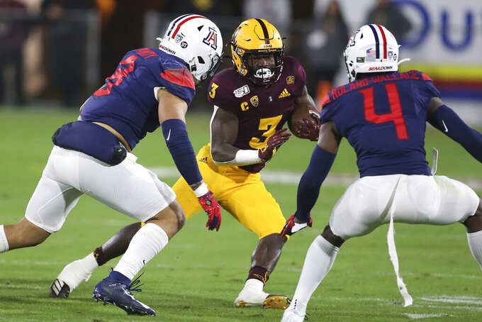 Arizona State's Eno Benjamin (3) is defended by Arizona's Anthony Pandy (8) and Christian Roland-Wallace (4) during the first half of an NCAA college football game, Saturday, Nov. 30, 2019, in Tempe, Ariz. (AP Photo/Darryl Webb)