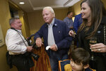 Former Gov.  Edwin Edwards greets photographer Travis Spradling, left, as he arrives with his wife Trina Edwards, right, to the election night results for current Louisiana Gov. John Bel Edwards at his election night watch party in Baton Rouge, La., Saturday, Nov. 16, 2019. (AP Photo/Matthew Hinton)