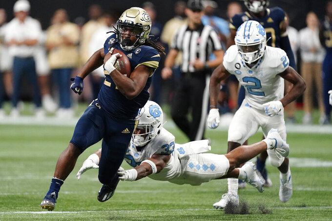 Georgia Tech running back Jordan Mason (27) tries to escape the grasp of North Carolina linebacker Cedric Gray (33) during the second half of an NCAA college football game, Saturday, Sept. 25, 2021, in Atlanta. (AP Photo/John Bazemore)