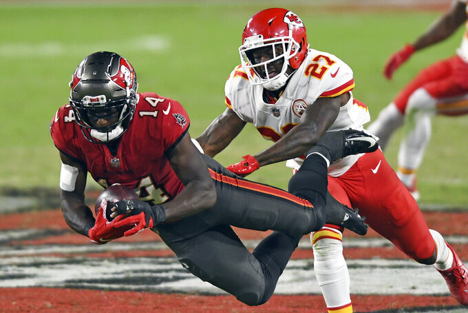 FILE - In this  Sunday, Nov. 29, 2020 file photo, Tampa Bay Buccaneers wide receiver Chris Godwin (14) makes a diving catch in front of Kansas City Chiefs cornerback Rashad Fenton (27) during the second half of an NFL football game in Tampa, Fla. Applying franchise and even transition tags to players can have major ramifications on a team's present and future. That was never more of a consideration than this year, with the salary cap decreasing by, for now, $18 million. That's the first time the cap has gone down, which is due to lost revenues caused by the COVID-19 pandemic.(AP Photo/Jason Behnken, File)