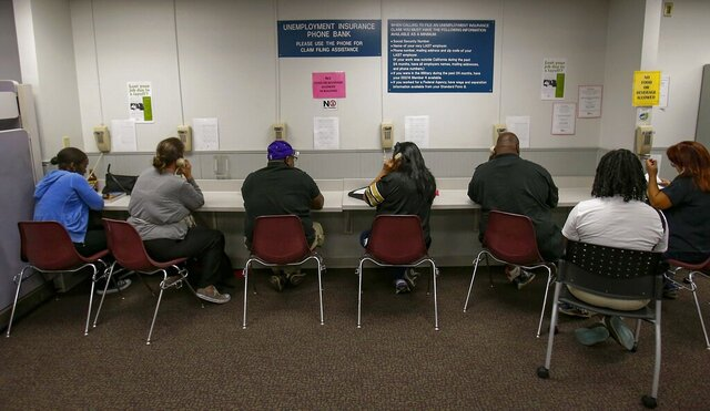 FILE - In this Sept. 20, 2013, file photo, visitors use the Unemployment Insurance phone bank at the California Employment Development Department, EDD office in Sacramento, Calif. The EDD office will not accept new unemployment claims for the next two weeks as the state works to prevent fraud and reduce a backlog as more than 2 million people are out of work statewide during the coronavirus pandemic, officials said late Saturday, Sept. 20, 2020. Nearly 600,000 Californians are part of a backlog where their unemployment claims have not been processed by the state's EDD for more than 21 days, the state said in a news release.  (AP Photo/Rich Pedroncelli, File)