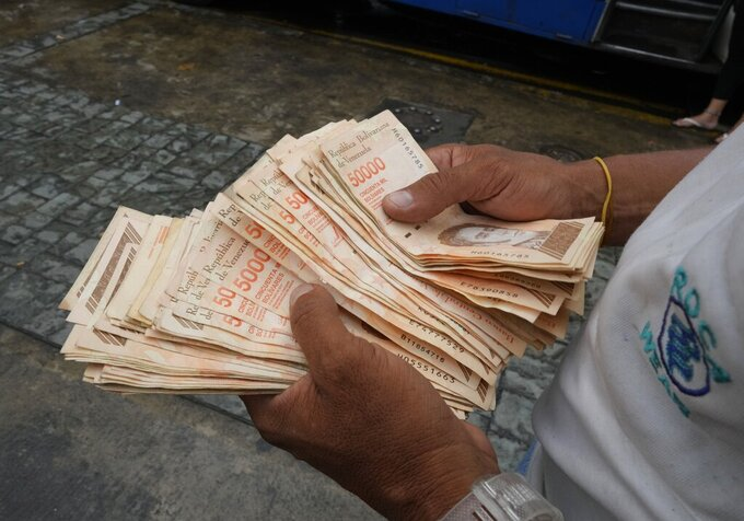 A man counts Bolivar bills that amount to $1, at a bus stop in Caracas, Venezuela, Thursday, Aug. 5, 2021. Venezuela says it will make a million-to-1 change in its currency soon, eliminating six zeros from the local currency as hyperinflation continues to plague the troubled South American nation. (AP Photo/Ariana Cubillos)