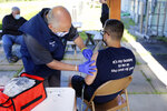 Howie McCausland, left, of the Mad River Valley Ambulance Service prepares to vaccinate Caleb Carrien, 19, of Barre, Vt., at a COVID-19 vaccination clinic held on Thursday June 17, 2021 in Waterbury, Vt. The state of Vermont was the first state to vaccinate 80% of the eligible population and a big reason the state reached the goal was by offering a variety of small, local vaccination clinics. The four-hour clinic at the the Waterbury offices SunCommon vaccinated seven people. (AP Photo/Wilson Ring)