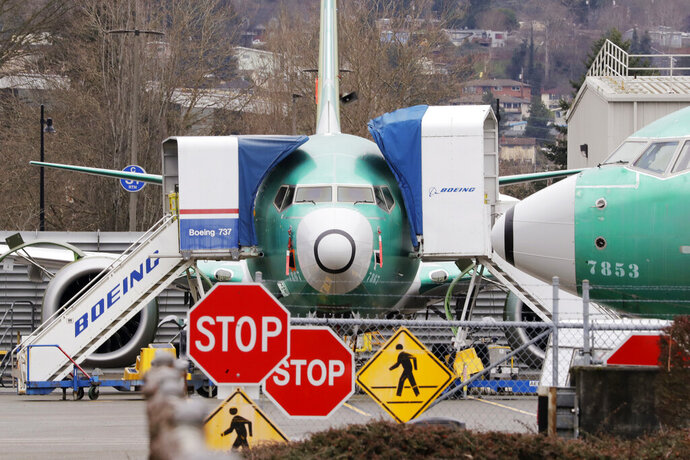 FILE - In this Monday, Dec. 16, 2019, file photo, Boeing 737 Max jets sit parked in Renton, Wash. American Airlines said Tuesday, Jan. 14, 2020, that it is removing the Boeing 737 Max from its schedule for two more months and canceling nearly 20,000 flights through early June, an acknowledgment of the ongoing uncertainty over when the grounded plane will fly again. (AP Photo/Elaine Thompson, File)