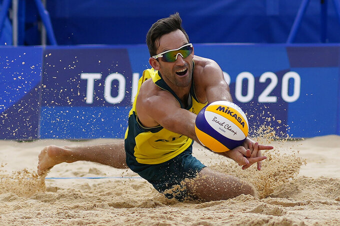 Damian Schumann, of Australia, dives for he ball during a men's beach volleyball match against the Russian Olympic Committee at the 2020 Summer Olympics, Monday, July 26, 2021, in Tokyo, Japan. (AP Photo/Petros Giannakouris)