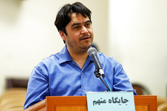In this June 2, 2020 photo, journalist Ruhollah Zam speaks during his trial at the Revolutionary Court, in Tehran, Iran. Iran. The judiciary spokesman, Gholamhossein Esmaili, announced Tuesday, June 30, 2020 that Zam, a journalist whose online work helped inspire the 2017 economic protests and who returned from exile to Tehran was sentenced to death. The Persian writing on the podium reads,