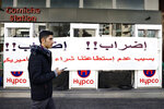 A man passes by a gas station that is closed during a protest against tight supply of dollars from the central bank in Beirut, Lebanon, Friday, Nov. 29, 2019. The Arabic banner reads:
