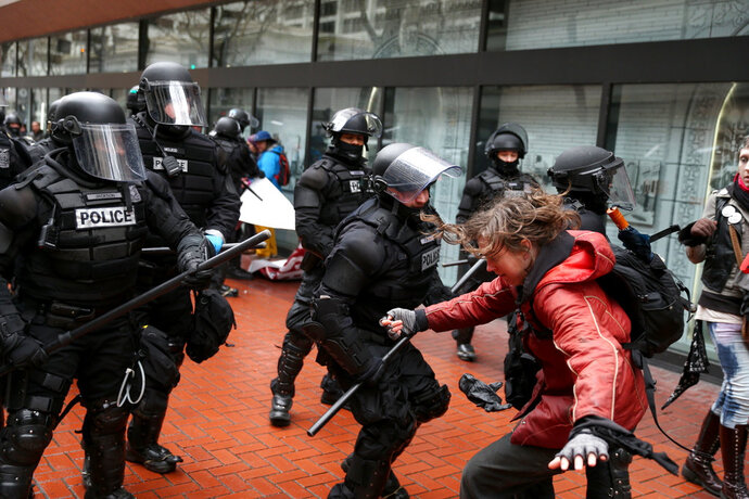 FILE - In the Feb. 20, 2017, file photo, protesters clash with police in Portland, Ore. Portland Mayor Ted Wheeler said frequent protests that predictably erupt into brawling fistfights between demonstrators have driven him and Police Chief Danielle Outlaw to seek new restrictions that, if enacted, would allow him to dictate where and when certain groups could rally. (Dave Killen /The Oregonian via AP, File)