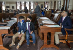 Armando Walle, 10, left, and his brother Joaquin Walle accompany their father state Rep. Armando Walle, D- Houston, right, on the House floor at the Capitol on the next-to-last day of the 87th Texas Legislature on Sunday May 30, 2021. (Jay Janner/Austin American-Statesman via AP)