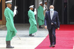 Mauritanian President Mohamed Ould Ghazouani wears a face mask as he walks past a guard of honor to welcome the French president upon arrival at Nouakchott Oumtounsy International Airport Tuesday June 30, 2020, in Nouakchott, to attend a G5 Sahel summit. Leaders from the five countries of West Africa's Sahel region, Burkina Faso, Chad, Mali, Mauritania and Niger, meet with French President Emmanuel Macron and Spanish Prime Minister Pedro Sanchez in Mauritania's capital Nouakchott on Tuesday to discuss military operations against Islamic extremists in the region, as jihadist attacks mount. The five African countries, known as the G5, have formed a joint military force that is working with France, which has thousands of troops to battle the extremists in the Sahel, the region south of the Sahara Desert. (Ludovic Marin, Pool via AP)