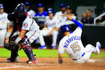 Kansas City Royals' Whit Merrifield (15) slides safely past Minnesota Twins catcher Willians Astudillo, left, during the fifth inning of a baseball game at Kauffman Stadium in Kansas City, Mo., Friday, Sept. 27, 2019. Merrifield scored on a sacrifice fly by Royals designated hitter Jorge Soler. (AP Photo/Orlin Wagner)