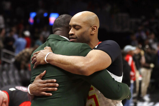 Atlanta Hawks guard Vince Carter, right, hugs former Hawk Dominique Wilkins as he leaves the court following an NBA basketball game against the New York Knicks Wednesday, March 11, 2020, in Atlanta. (AP Photo/John Bazemore)
