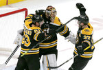 Boston Bruins goaltender Tuukka Rask (40) is congratulated by teammates Brad Marchand (63) and Patrice Bergeron (37) after defeating the Florida Panthers in an NHL hockey game, Thursday, March 7, 2019, in Boston. (AP Photo/Mary Schwalm)