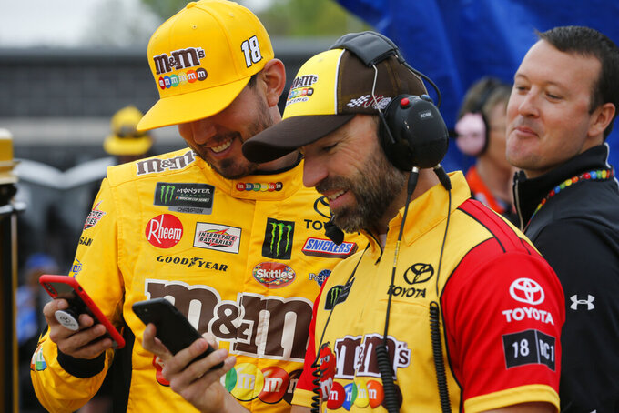 Kyle Busch, left, and his crew chief, Adam Stevens, laugh on their phones prior to qualifying for Saturday's NASCAR Cup auto race at Richmond International Raceway in Richmond, Va., Friday, April 12, 2019. (AP Photo/Steve Helber)