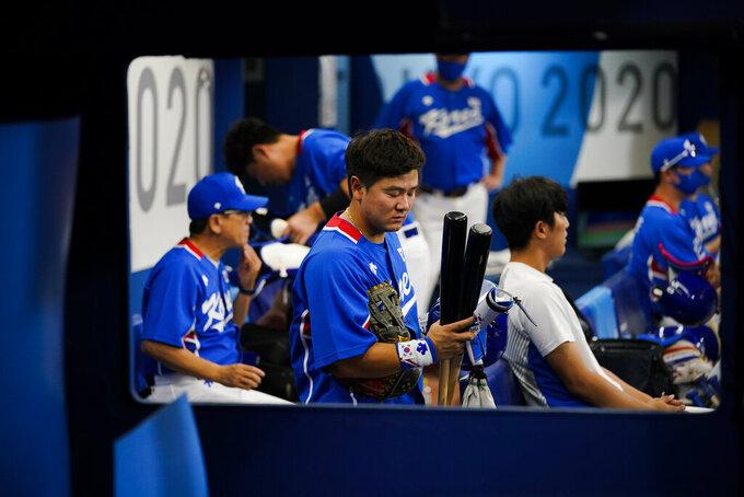 South Korea's Joohwan Choi packs up after a semi-final baseball game against the United States at the 2020 Summer Olympics, Thursday, Aug. 5, 2021, in Yokohama, Japan. The United States won 7-2. (AP Photo/Sue Ogrocki)
