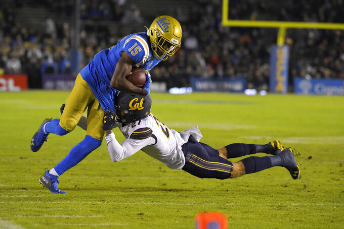 UCLA wide receiver Jaylen Erwin, left, breaks a tackle by California safety Ashtyn Davis before heading in for a touchdown during the first half of an NCAA college football game Saturday, Nov. 30, 2019, in Pasadena, Calif. (AP Photo/Mark J. Terrill)