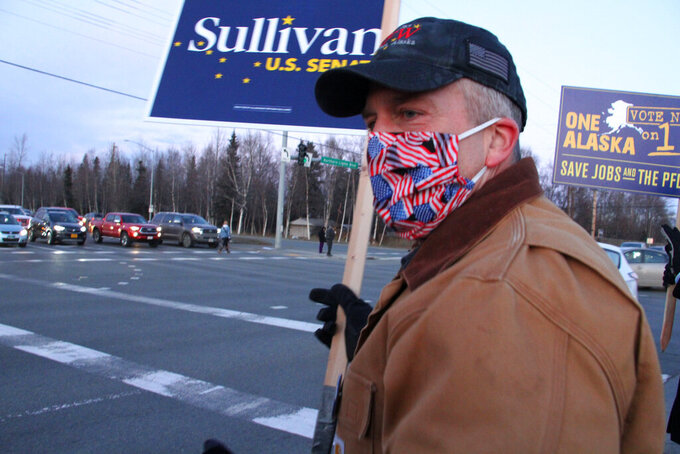 U.S. Sen. Dan Sullivan, an Alaska Republican seeking reelection, waves a sign at a busy intersection Monday, Nov. 2, 2020, in Anchorage, Alaska. Sullivan in the Nov. 3, 2020, election faces Dr. Al Gross, an independent who won the Alaska Democratic primary. (AP Photo/Mark Thiessen)