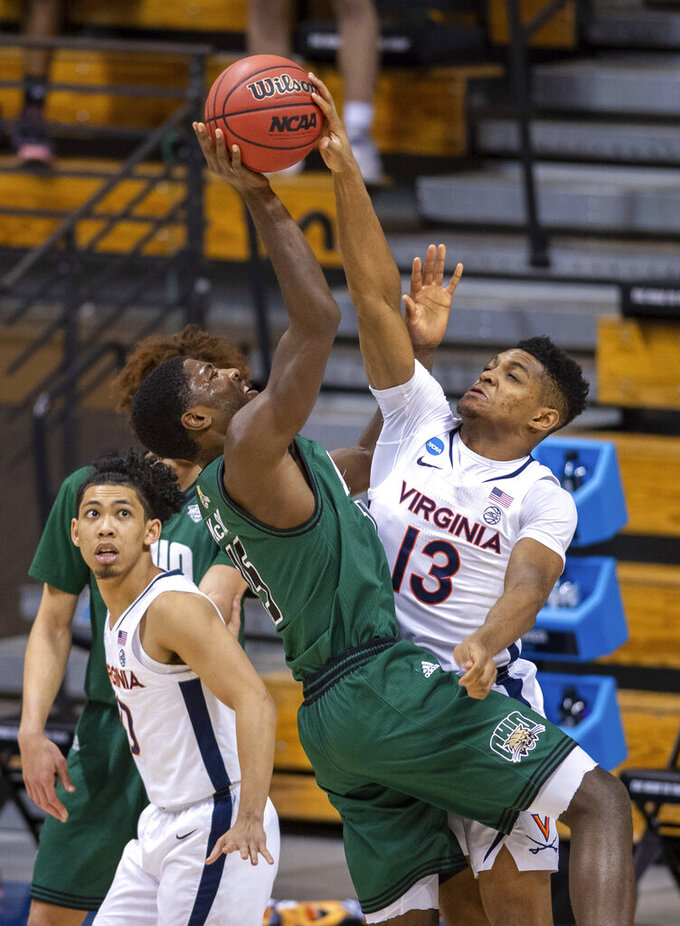 Ohio guard Lunden McDay (15) puts up a shot that is blocked by Virginia guard Casey Morsell (13) during the second half of a first-round game in the NCAA men's college basketball tournament, Saturday, March 20, 2021, at Assembly Hall in Bloomington, Ind. (AP Photo/Doug McSchooler)