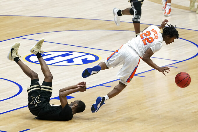 Florida's Tyree Appleby (22) falls over Vanderbilt's Trey Thomas, left, in the second half of an NCAA college basketball game in the Southeastern Conference Tournament Thursday, March 11, 2021, in Nashville, Tenn. (AP Photo/Mark Humphrey)