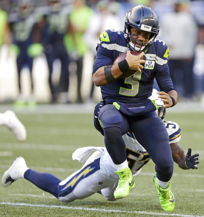 FILE - In this Nov. 4, 2018, file photo, Seattle Seahawks quarterback Russell Wilson (3) tries to get past Los Angeles Chargers' Jatavis Brown during the second half of an NFL football game, in Seattle. Russell Wilson won a playoff game with Seattle as a rookie, a Super Bowl in his second season and another NFC championship the third time around. The best Dak Prescott can hope for with the Dallas Cowboys is to join Wilson on that list of Super Bowl winners in his third year, a quest that will start with the first postseason meeting of quarterbacks with quite a bit in common, other than postseason pedigree.(AP Photo/Scott Eklund, File)