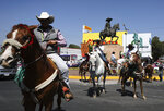 Charros, as Mexican cowboys are known, sit on their horses after paying tribute to Mexican revolutionary leader Emiliano Zapata, near a statue of him, top, in Mexico City, Wednesday, April 10, 2019. Mexico marked the 100th anniversary on Wednesday of the assassination of Emiliano Zapata, one of the main heroes of the 1910-1917 revolution who was gunned down by government soldiers over his unyielding defense of peasants. (AP Photo/Eduardo Verdugo)