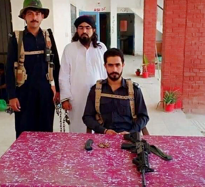 In this photo released by Police Department of Lakki Marwat, shows police officers pose for photograph with handcuffed a cleric Mufti Sardar Ali Haqqani, center, with confiscated weapon, who threatening to kill the Malala Yousafzai, after his arrest at a police station in Lakki Marwat, a district in the Pakistan's northwestern Khyber Pakhtunkhwa province, Thursday, June 10, 2021. Pakistani police have arrested cleric Haqqani after a video of him went viral on social media, in which he threatens Nobel Laureate Malala Yousafzai over her recent comments about marriage, officials said Thursday. (Police Department of Lakki Marwat via AP)
