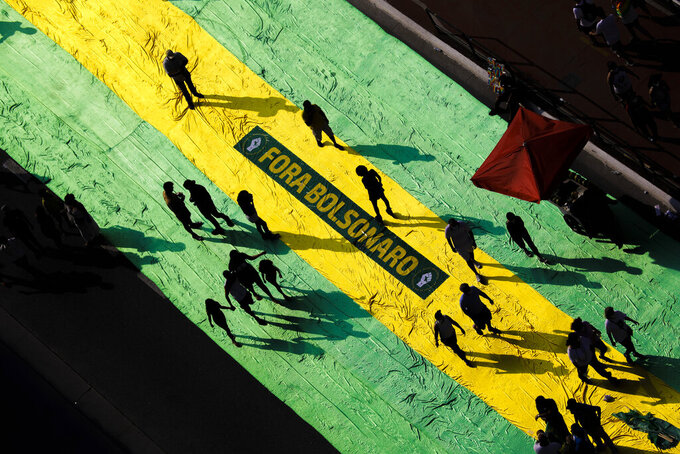 """Protestors walk on a giant banner that reads in Portuguese """"Bolsonaro Out,"""" during a protest against President Jair Bolsonaro, at Paulista Avenue, Sao Paulo, Brazil, Sunday, Sep. 12, 2021. (AP Photo/Marcelo Chello)"""