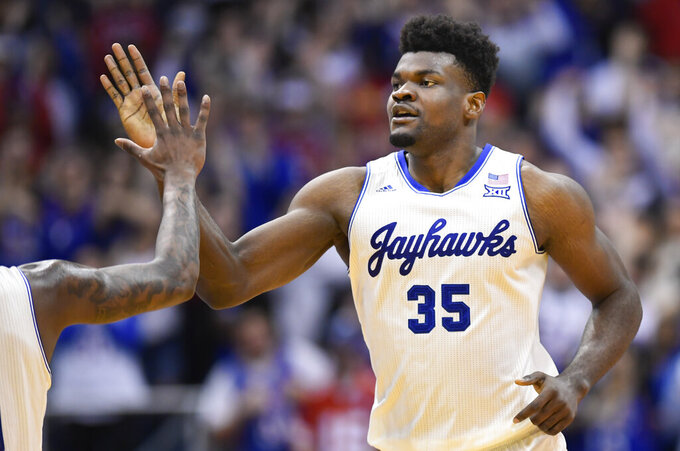 Kansas center Udoka Azubuike (35) is congratulated after a dunk against Texas during the second half of an NCAA college basketball game in Lawrence, Kan., Monday, Feb. 3, 2020. (AP Photo/Reed Hoffmann)