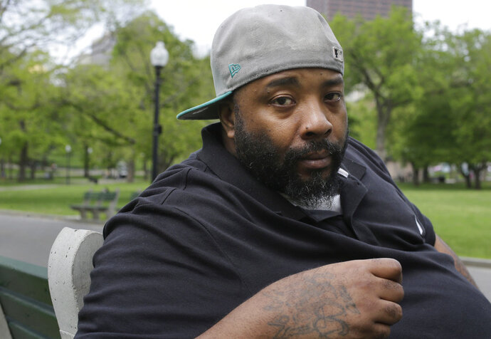 In this Wednesday, May 16, 2018 photo Emory Ellis, of Boston, sits for a photo in a park, in Boston. Ellis was arrested in 2015 after he tried to buy breakfast at Burger King using a $10 bill that the cashier thought was fake. Ellis' arrest resulted in a probation violation that landed him in jail for three months before prosecutors dropped the charge when authorities determined the bill was real.  Ellis is suing Burger King accusing them in a lawsuit filed this week of discriminating against him because he's black and homeless. (AP Photo/Steven Senne)